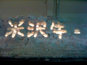 A local merchant has carved his trend into the snow outside his shop with candles and shovels; it says 'Yonezawa Beef'