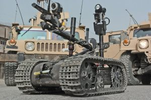 A Talon MTRS (man-transportable robotic system) robot that is used by the US Navy (USN) Explosive Ordnance Disposal Mobile Unit 6 (EODMU-6), Detachment (DET) 10, to safely inspect ordnance and situations unsafe for EOD tech personnel, at the site of an Improvised Explosive Device detonation. A US Navy (USN) technician is controlling the Talon from one of the High-Mobility Multipurpose Wheeled Vehicles (HMMWV) in the background during Operation IRAQI FREEDOM.